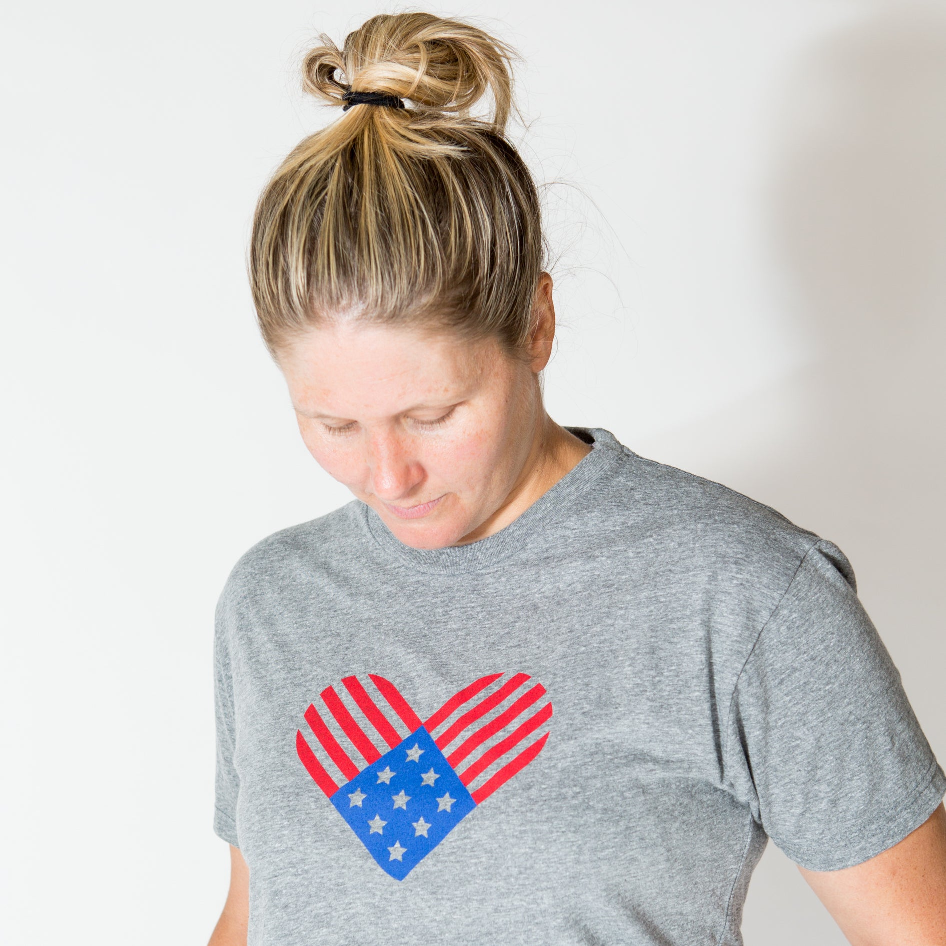 Woman with head looking down at the red and blue version of the american flag on a tee-shirt.