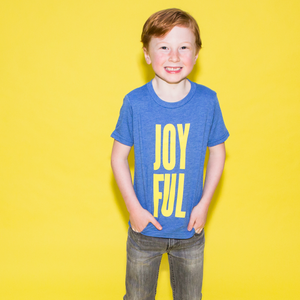 "Young boy wearing a blue t-shirt with ""Joyful"" in yellow print. The word is spread across two lines: JOY on top and FUL on the bottom."