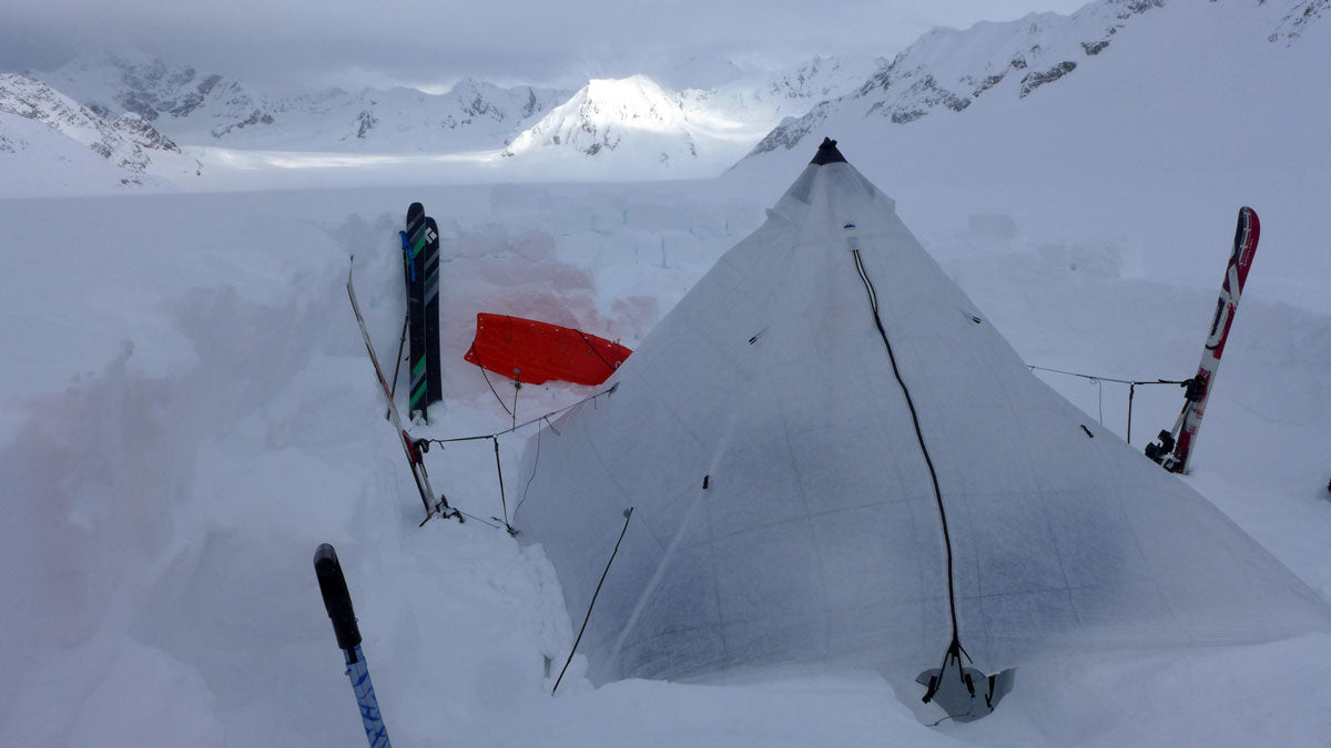 An ultralight pyramid tent set up for winter backpacking in Alaska.