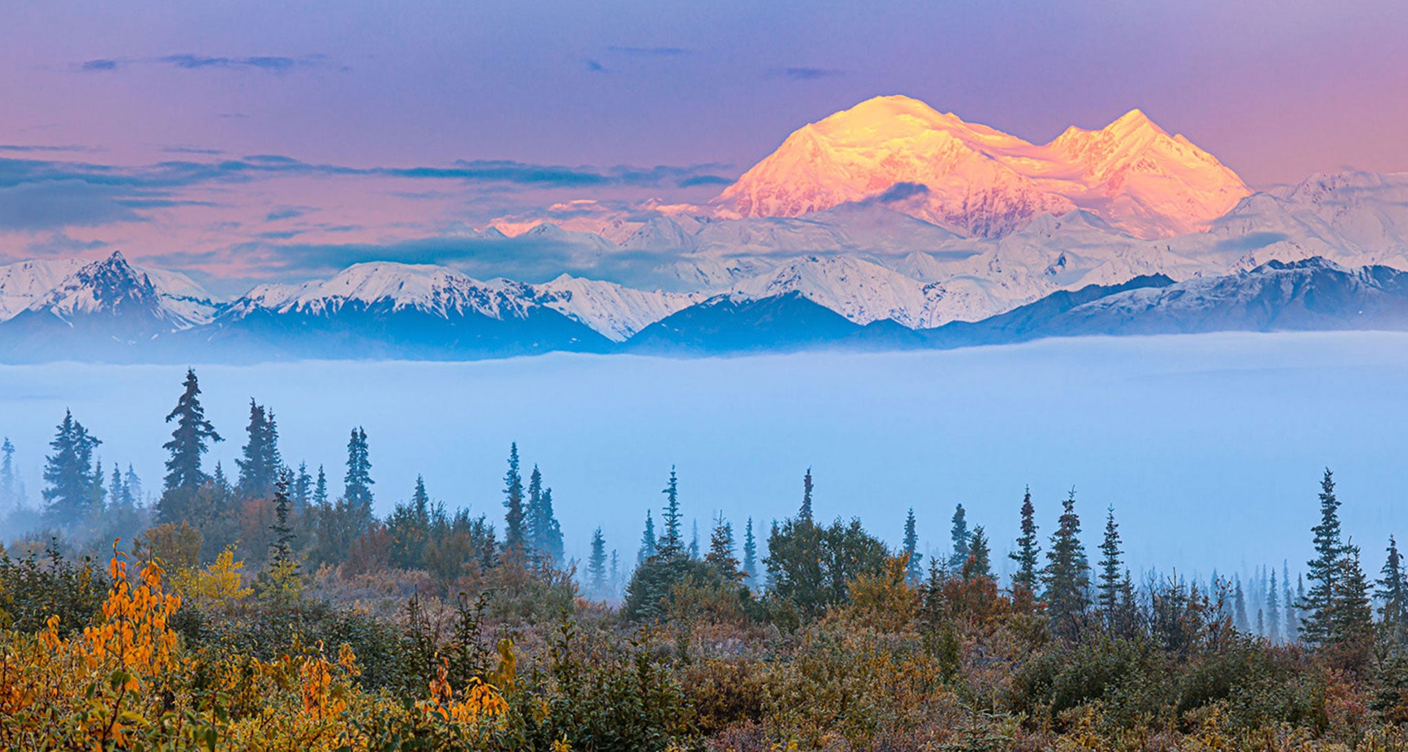 Sunrise on the eastern face of Denali and the Alaska Range reveals itself after a typical prolonged period of clouds and rain.  The only significant cloud left in the wake of this wet system is fog and stratus trapped on the valley floor under a temperature inversion.  Alaska has an abundance of low level moisture from lakes, rivers, wetlands and the ocean.