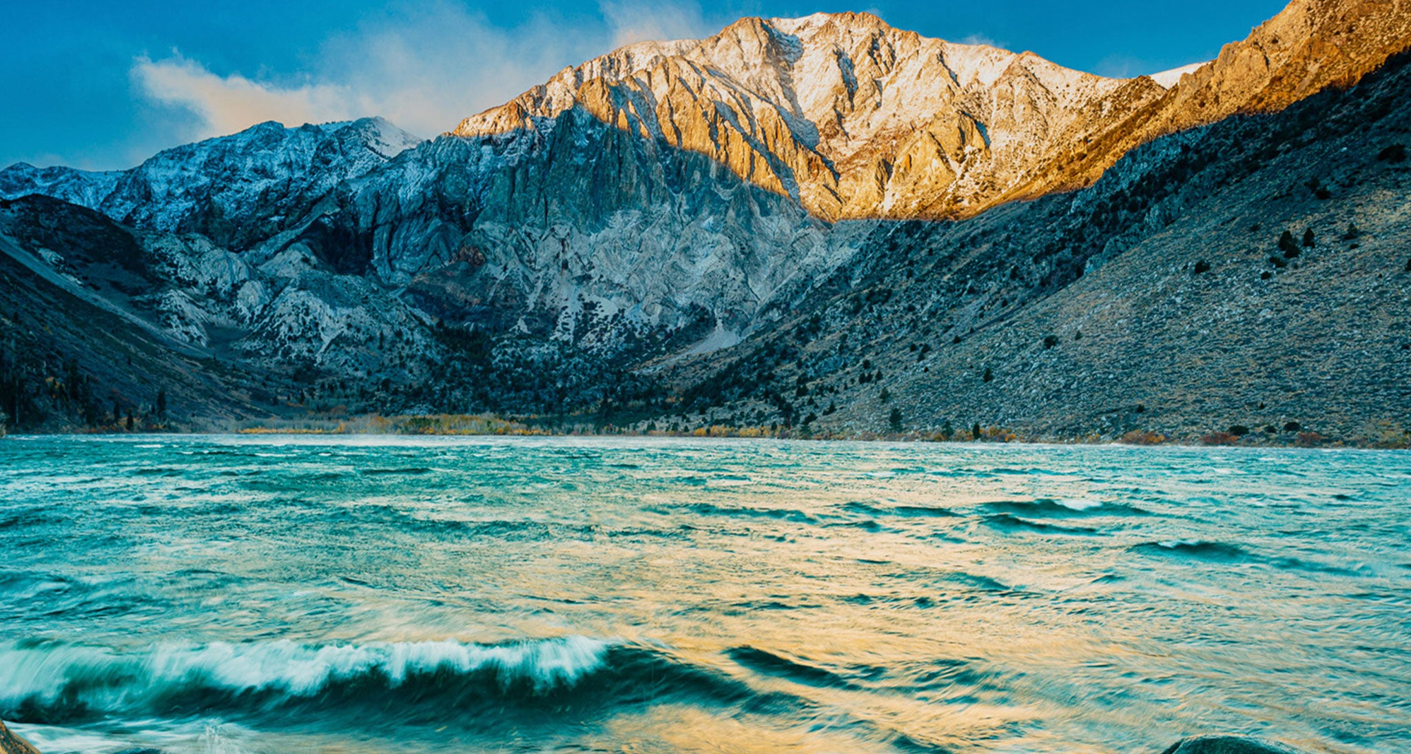 A stiff west wind at sunrise blows across Convict Lake in the Eastern Sierra, CA.  This is a downslopping wind.  Strong winds blowing across a mountain range flow downward on the lee side of the range as seen here.  Downsloping winds are drying winds and the western slope of the Sierra which would be on the windward side is probably  experiencing considerable cloud cover and precipitation.  Winds accelerate when they descend and accelerate even more when they blow across a surface with reduced friction such as a lake.  The high Sierra is the most prominent and formidable terrain barrier in the CONUS.  They are the reason why the Owen's Valley in their eastern shadow is a desert.
