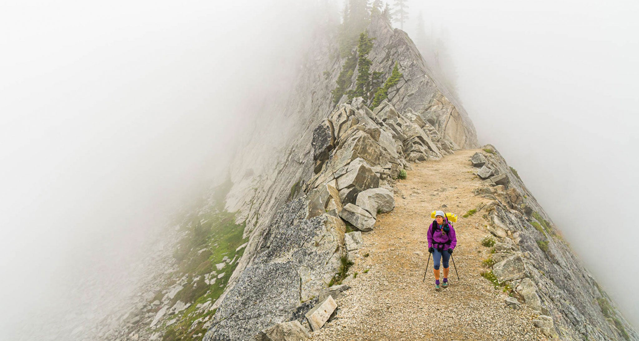 It looks like this southbound Pacific Crest Trail hiker on the Kendall Catwalk in the Alpine Lakes Wilderness, Washington is in the fog but she is not.  She is engulfed in a stratocumulus cloud in a stable atmosphere, who's base is below ridge top level.   A shallow, low level onshore flow  being lifted by the abrupt rise of the Cascades frequently causes this on the west facing slopes of the range.  This is a high pressure cloud with little vertical development capped by a temperature inversion at the top of the cloud layer. There was no precipitation falling from this cloud and we descended well below the base with unlimited visibility within an hour of making this image.
