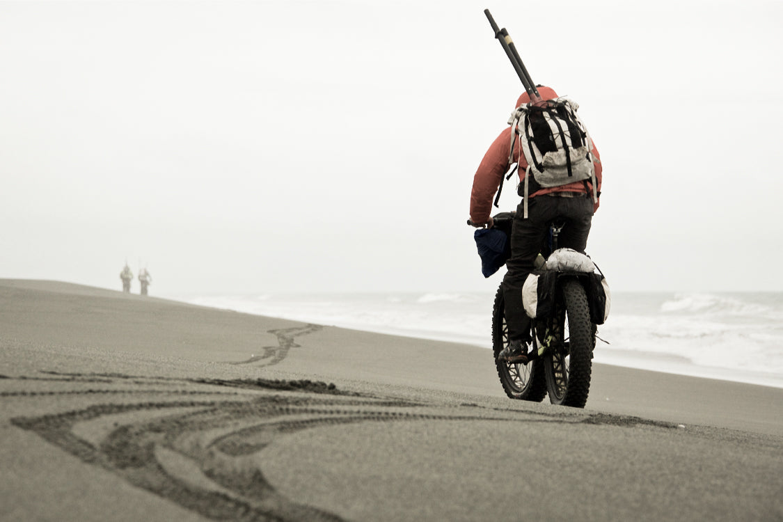 A rider bikepacking on a fat bike with an ultralight backpack on a rainy day along the southeastern coast of Alaska.