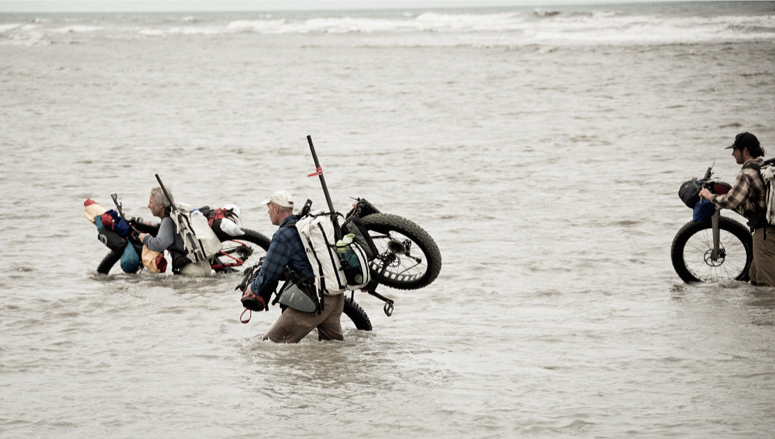 Three men ford a river on Alaska's Lost Coast carrying their bikepacking bikes.