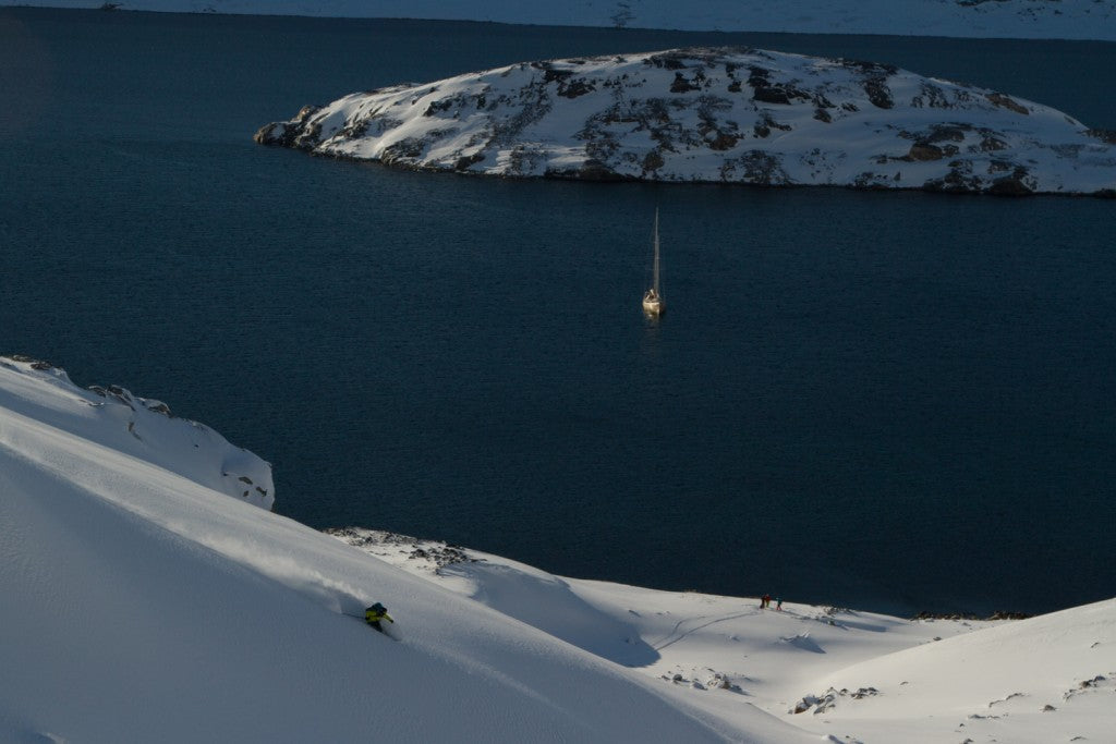 Nat Segal skiing perfect powder in West Greenland, with the La Louise sailboat below.