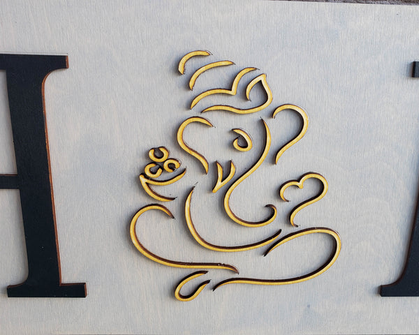 Round wood sign with HME letters and Ganesh as the interchangeable O
