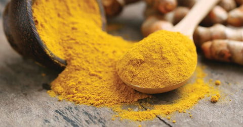 Powdered curcumin, with turmeric roots in the background, to show how it's normally eaten