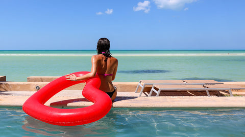 Woman sitting poolside in swimwear holding onto red heart shaped float with her left arm.