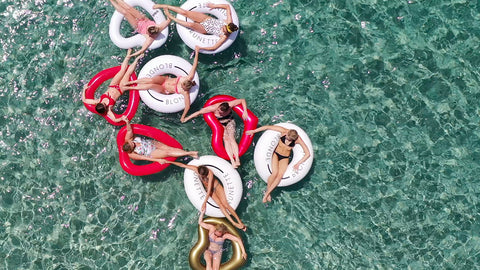 Aerial shot of nine friends in the shallow clear ocean water, floating in red and white floats, all holding hands.