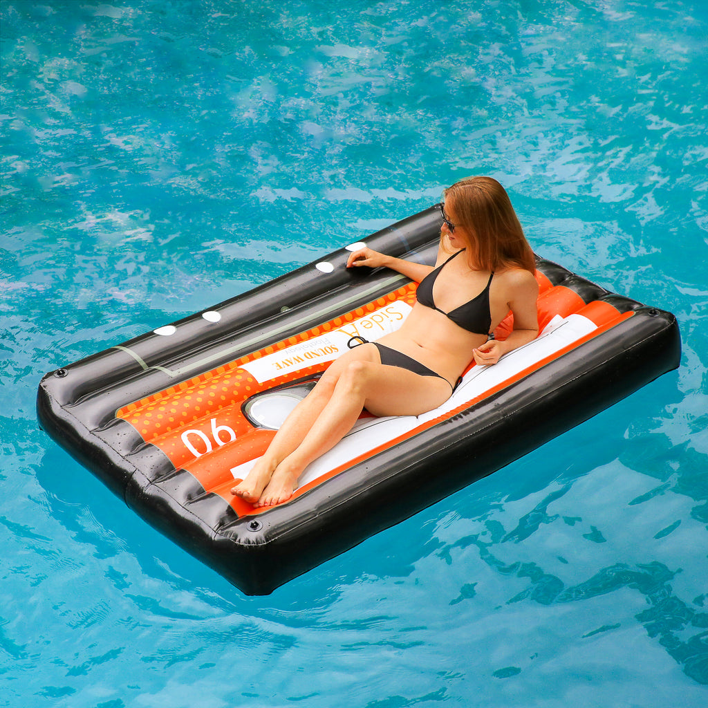 Woman in black swimwear floating on a black cassette float in the center on a pool. She is propped up on her elbows and looking into the distance.
