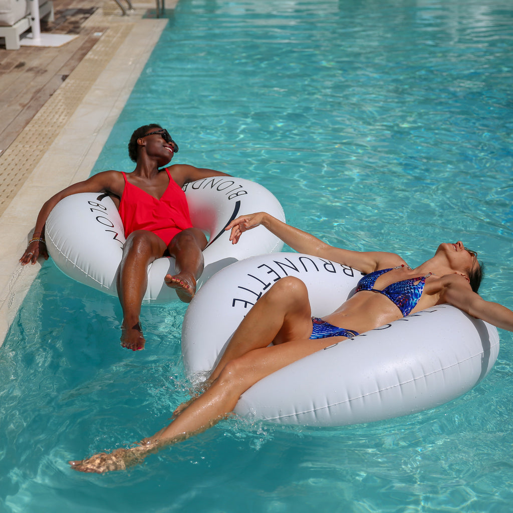 Two women floating near the edge of the pool in white pool rings that have the word blonde on one and brunette on the other. Each woman is smiling and has their head back and arms out.