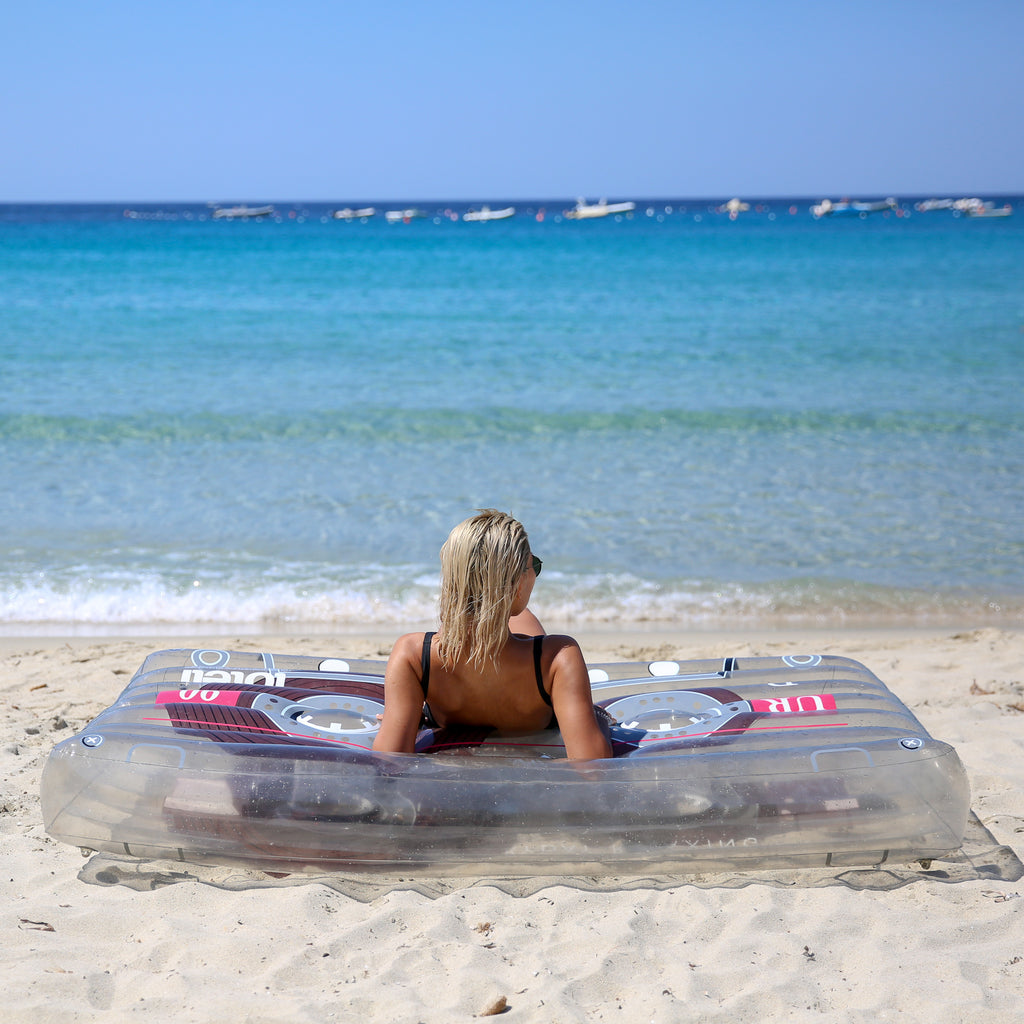 Woman lying on her back propped up on her elbows on top of a clear cassette pool float staring out at the ocean.
