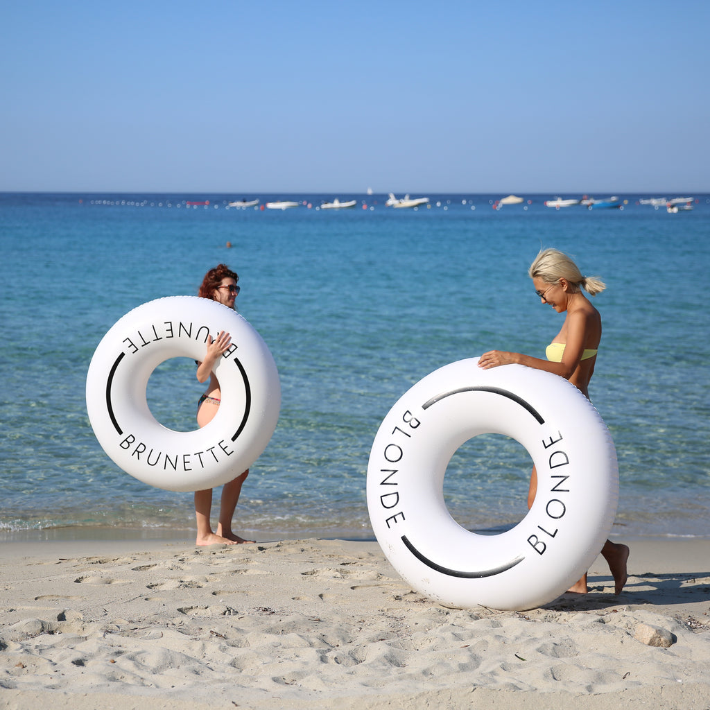 Two women standing near the sea shore, woman on left is holding a white swim ring with the word brunette on it with her right arm. The woman on the right is laughing and leaning on a white swim ring with the word blonde on it.