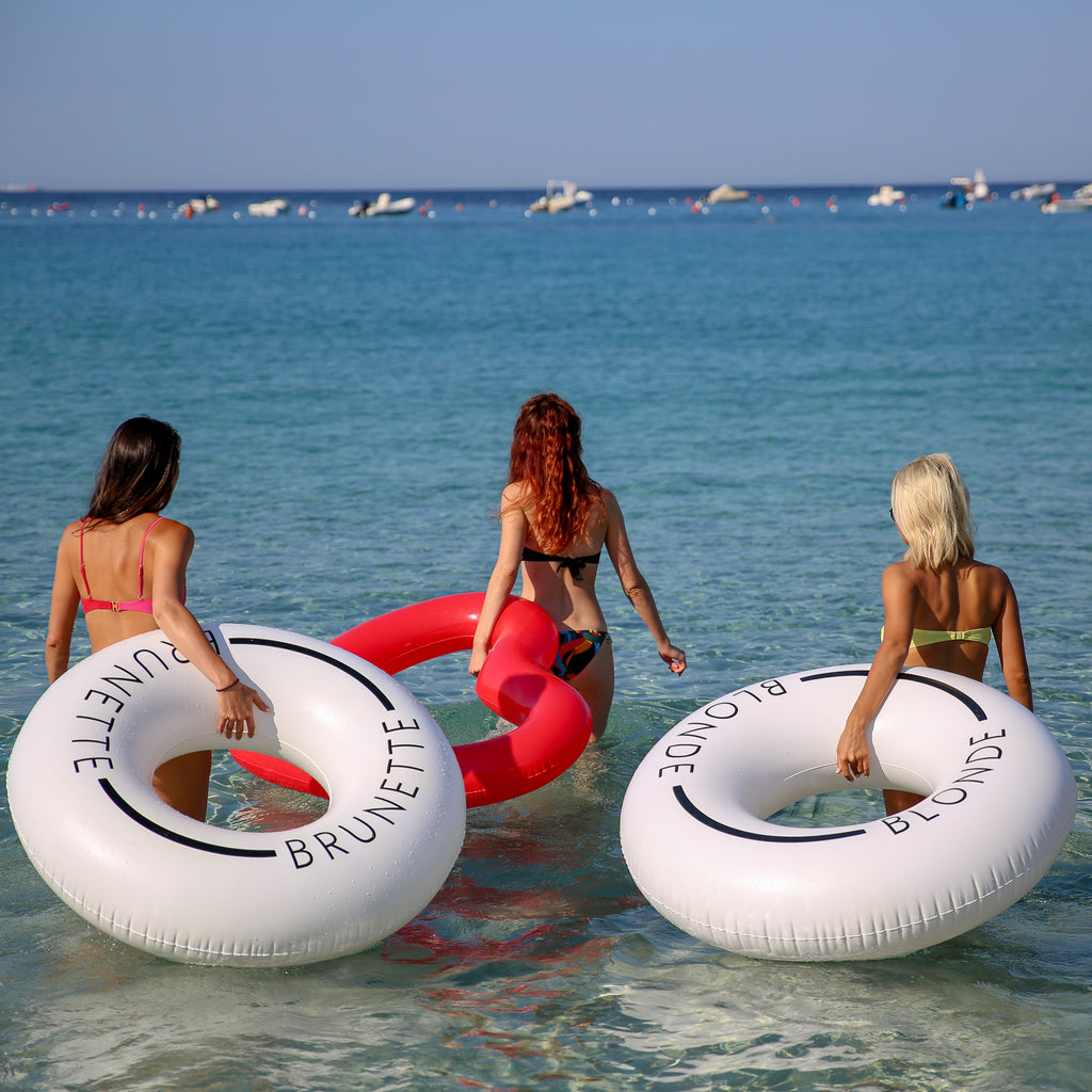 Three women walking with swim rings into the shallow ocean waters. The woman left is carrying a white swim ring with the word brunette on it. The center woman is holding a red heart shaped swim ring. The woman on the right is holding a white swim ring with the word blonde on it.