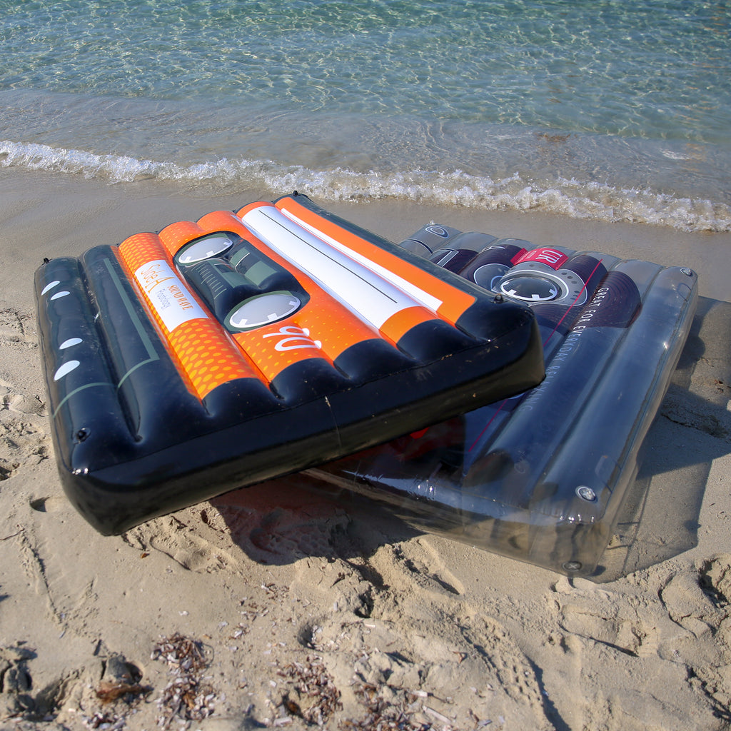 Two cassette pool floats on the edge of the shore. The black cassette is angled on top of the clear cassette pool float.