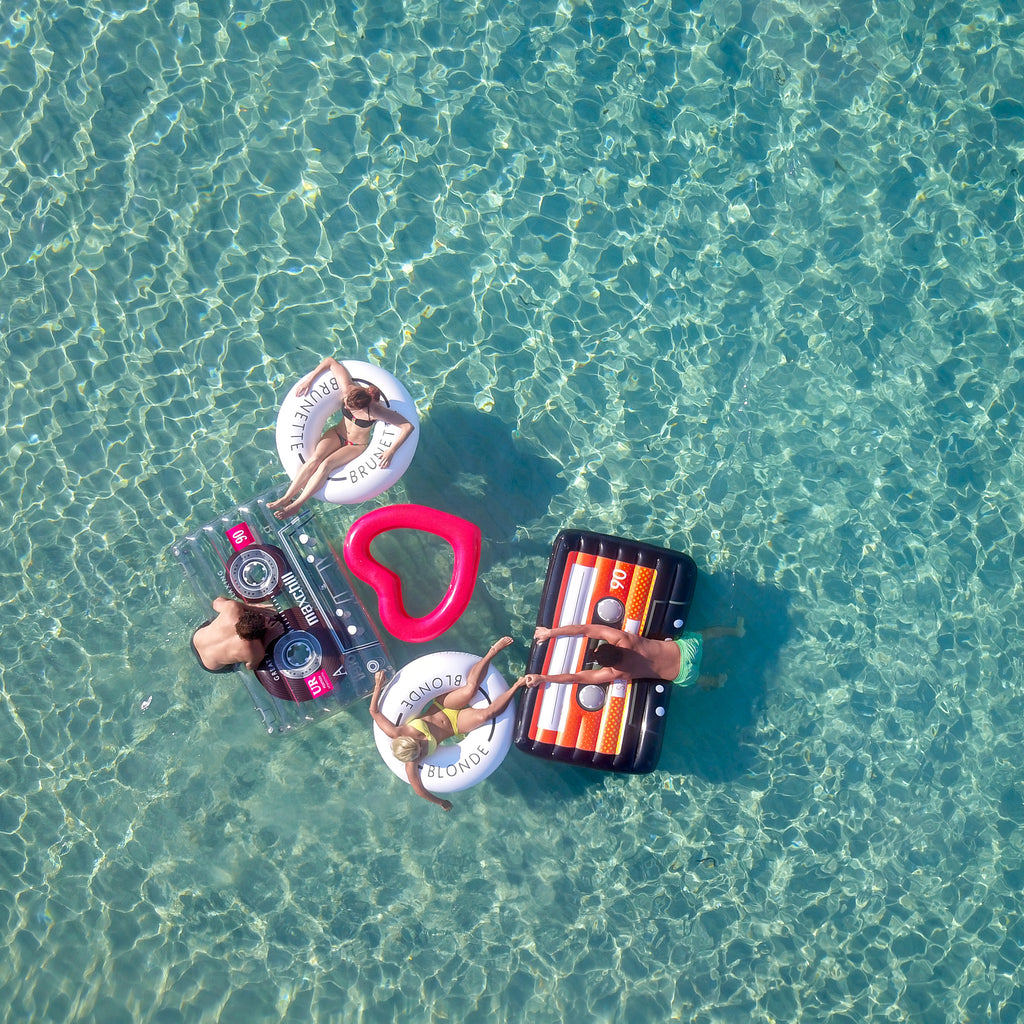 Aerial photo of two couples floating near to one another on top of five floats. Woman on left is sitting in a white swim ring with the word brunette on it. Her feet are resting on a clear cassette float that a man is leaning over onto from the water. The man on the right is reaching over a black cassette float from the water and holding onto the foot of a woman on a white swim ring with the word blonde on it. Between the two couples playing in the water there is a red heart shaped pool float.