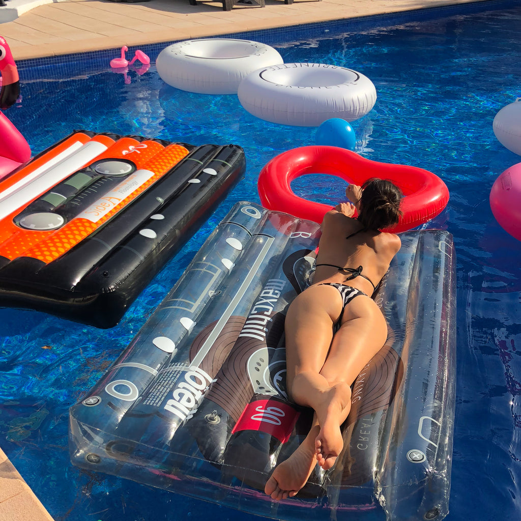 Photo of a woman floating on her stomach on a clear cassette float. She is facing away from the camera with her feet crossed. There are also several other loteli pool floats in the pool with the woman.