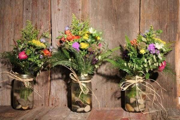 mason jars arrangement with river rocks and fall wild flower