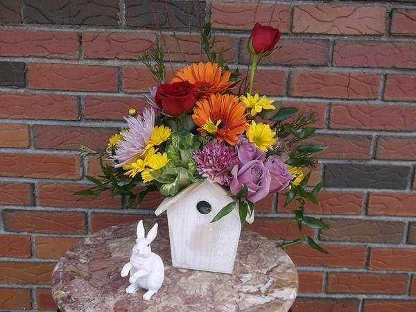 old wooden birdhouse re-purposed for fall flower arrangement