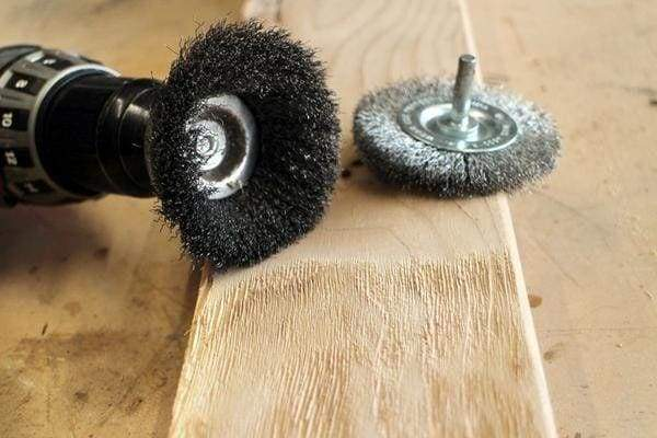 using a wire wheel brush to create a distressed rustic wood grain to new pine boards