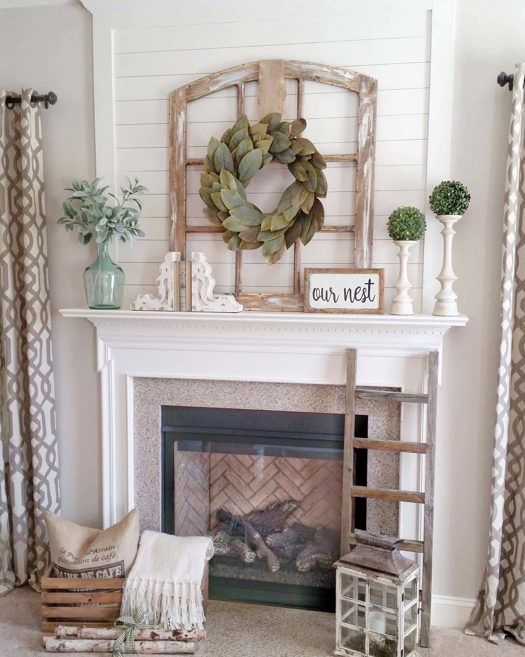 "A great flea market find, this rustic window frame makes for a great element in a modern farmhouse or rustic design. They simply leaned the window frame off the mantel and hung a small wreath of bay leaves from it. The simple ""Our Nest"" sign helps bring that warm cozy feeling to this rustic mantel space."