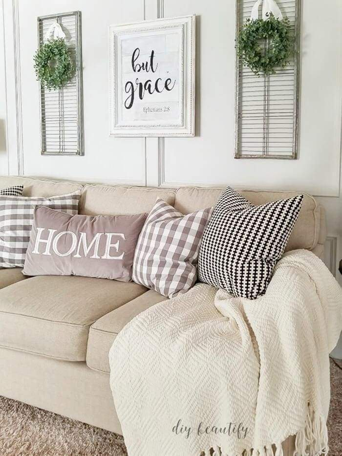 Here we see a pair of metal shutter, could easily have been an old set of wooden shutters. In this case they hang on either side of a bible verse created in a wonderful bold script sign. See how the decorator accented each shutter with a small greenery wreath. This grouping combines well with the beige sofa, pillows, and throw. Doesn't it just make you want to sit for a spell and relax.