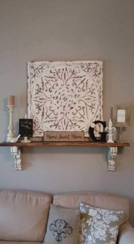 "The simple wooden shelf is held up by two distressed corbels and atop of it we find a combination of candlestick with pillar candle, a Fleur De Lis decoration, symbolic letter, and signs like ""home sweet home."" Behind this collection the decorator has place an old looking tin ceiling panel. Did you know you can buy these panels online and create this effect with a little paint and a sander? Colors seem to follow the common theme of white and beige with some accents of black."