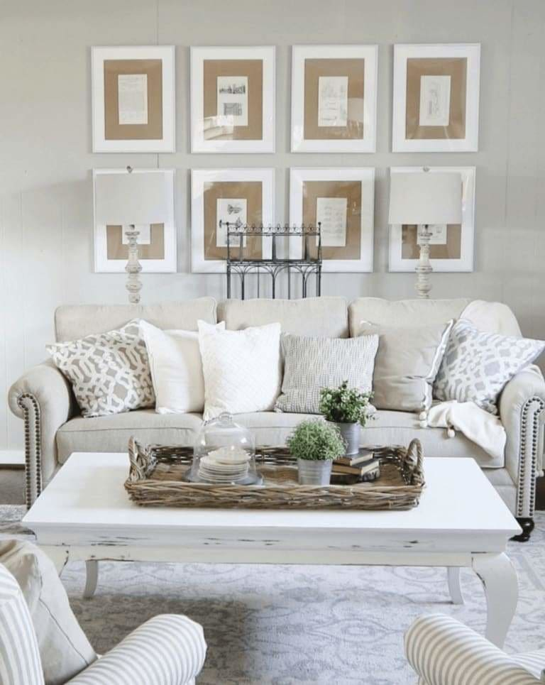 We like how this living room décor has created an understated balance combining the white frames with beige matting of these eight symmetrically placed photos. Notice how they flow well with the white and beige upholstery. It was simple to control colors in this room with the simple greenery pots on the coffee table.