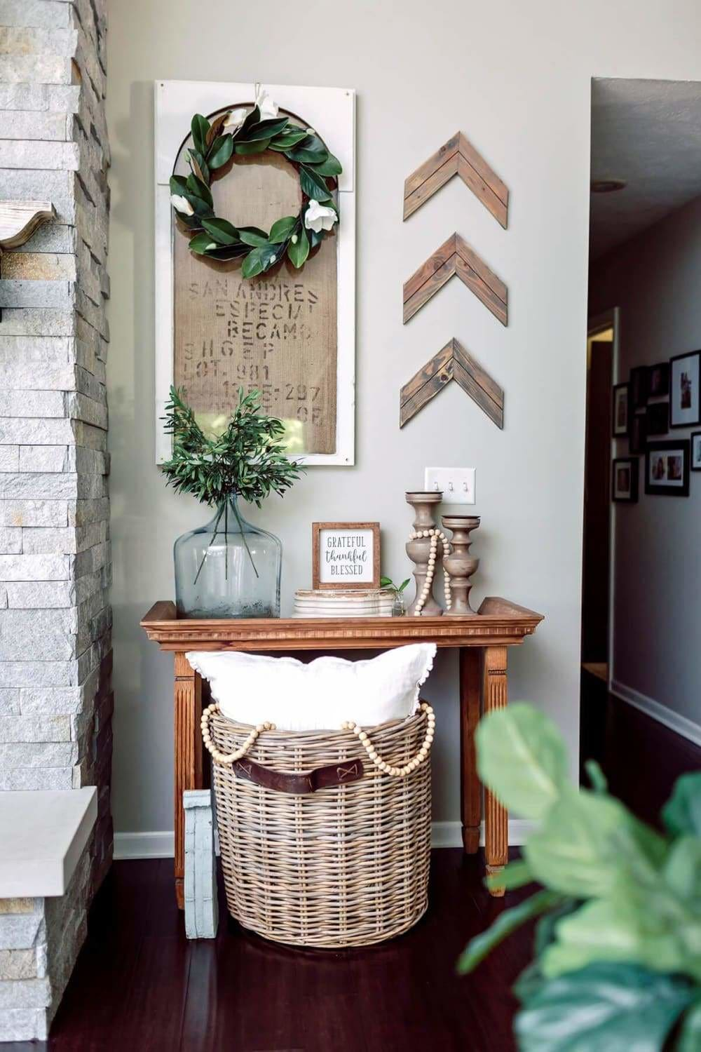 A perfect way to bring out the feel of rustic or modern farmhouse is with the use of old burlap sacks. Here the burlap sack is mounted over a painted white background to make it pop from the light gray walls. To create some color, they've used a bold green wreath with white blossoms hanging over the burlap sack. They took three rustic frame corners to create a chevron pattern and place them off to the side to create more contrast from the gray walls. The wooden table below along with the wicker basket filled with throws help bring together the warm rustic charm of the room.
