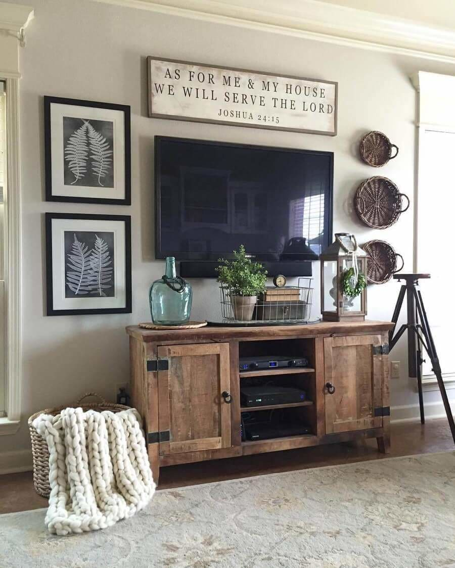 This entertainment area is highlighted with a very popular Bible verse used by many to find inspiration in there home. Again, we see balance in the use of different elements on each side of the TV. With black and white fern prints to one side and round wicker trays of varied sizes on the other. The weathered wooden console below ties everything together with another convenient storage area, this time for the TV's electronic devices.
