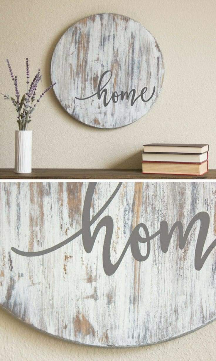 "Another good example of rustic distressed wood being the canvas for a simple scripted message. Here the sign background was cut into a circle and a distressed finish was created. The stenciled ""home"" script was then applied in a warm gray script. Here we see that simple can be a bold statement for both rustic and modern farmhouse décor."