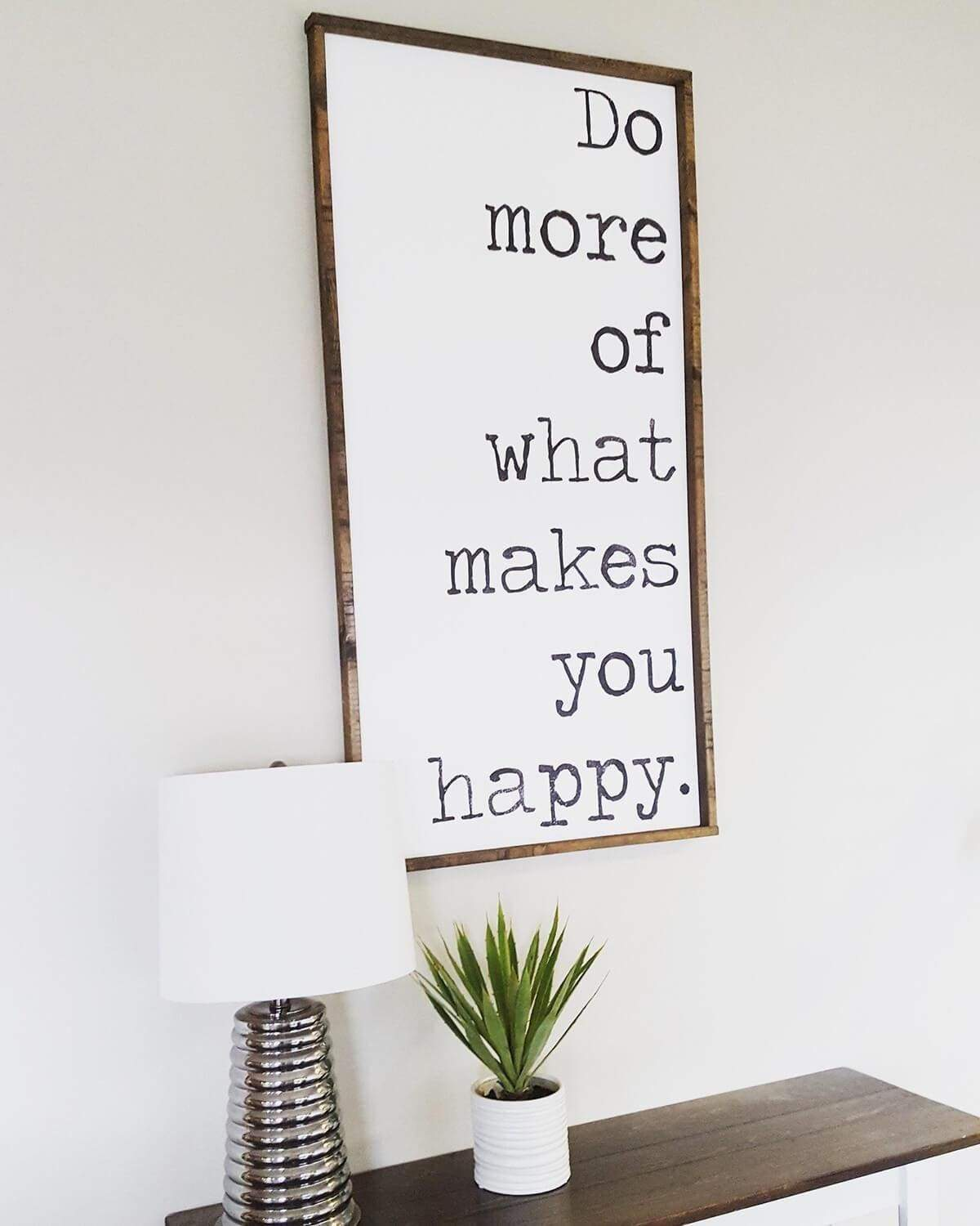 "They've created a wonderful sign with plain text in a typewriter font design. A great reminder to ""Do more of what makes you happy."" The simple shelf below holds a mirror-based lamp and simple small greenery pot."