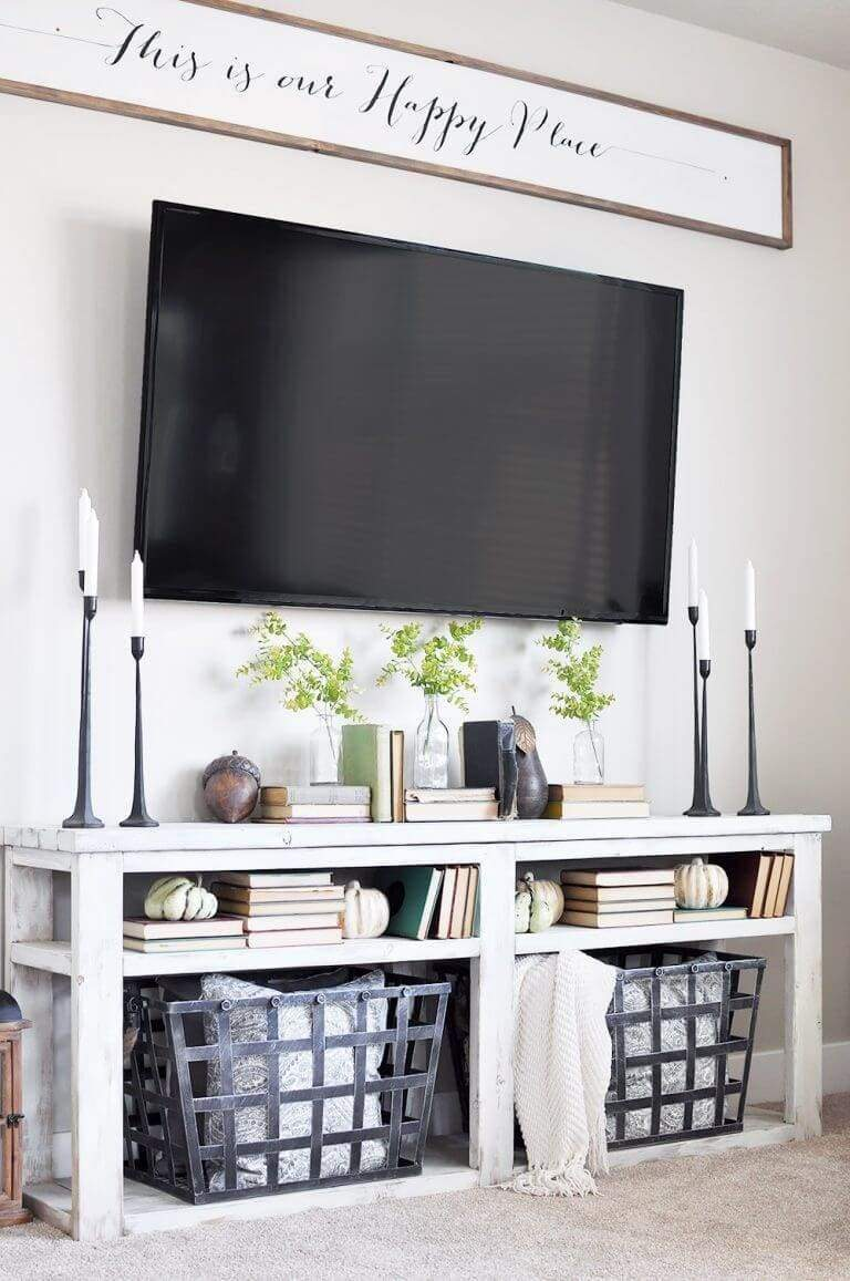 "Here's another example of a simple TV area made into an inviting rustic space with simple elements. An inviting sign hangs over the TV proclaiming ""This is our happy place."" Scripted letters on the sign create an old-fashioned feeling. There is a weathered looking console table with candles, greenery, and books directly below the TV. Notice the handy baskets below this console, great for throws and pillows."