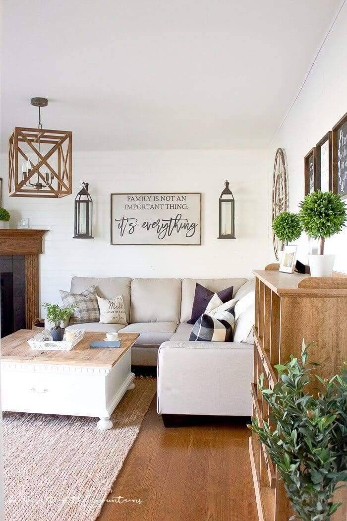 Want to bring rustic charm into your living room? This example brings it all together with the family centered sign hung over the sofa. Over from it we find an oversize wooden clock with chalkboard signs and family photos. Notice how the decorator used candle lanterns on each side of the focal piece sign.