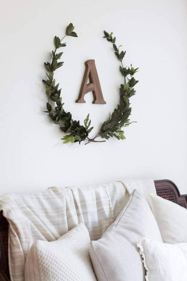 Looking for an understated way to display a family initial? This arrangement combines a wooden initial with a partial wreath created with faux myrtle leaves. Try mixing it up with different material for the letter or another wreath material and this understated arrangement will accent any farmhouse style bedroom or den.