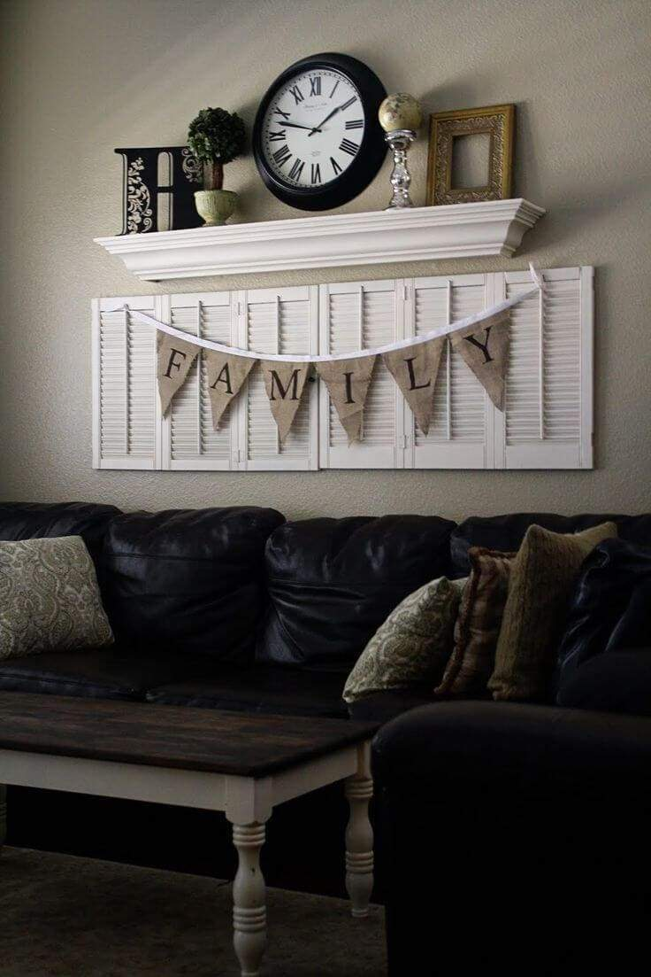 "Another interesting grouping begins with arranging a series of upcycled white shutters. They added a burlap banner with letters spelling out ""Family"" to spruce up the shutters. Above the shutters is mounted a clean white shelf. On this shelf are displayed an initial, faux topiary tree, a globe and an empty frame. The grouping is completed with a simple black and white clock in the center."