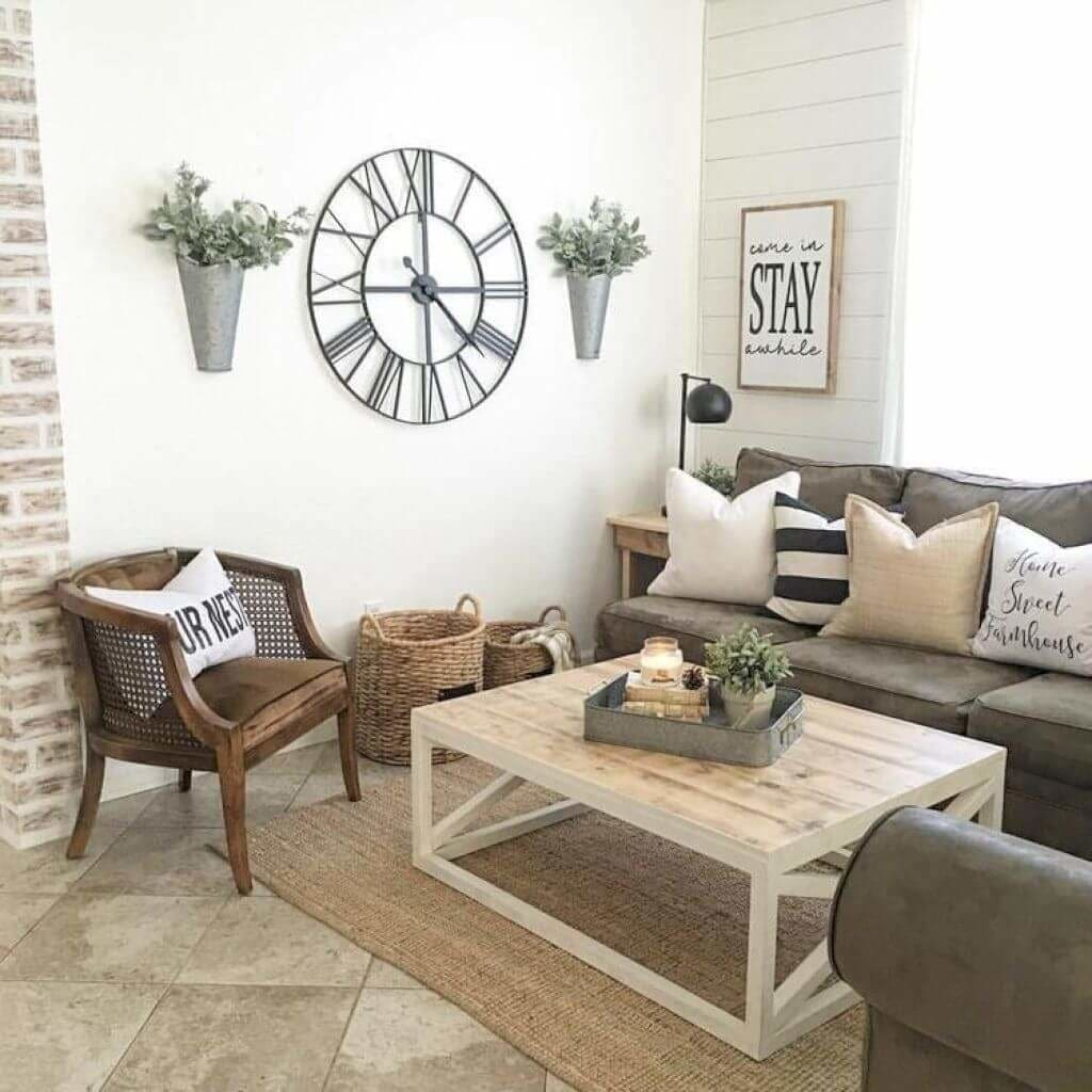 "Here are more galvanized wall vases with dried fall flowers and an oversize metal clock, have you noticed some common elements in many of these groupings. On the adjoining wall we see a sign inviting guests to ""Come in and stay a while."""