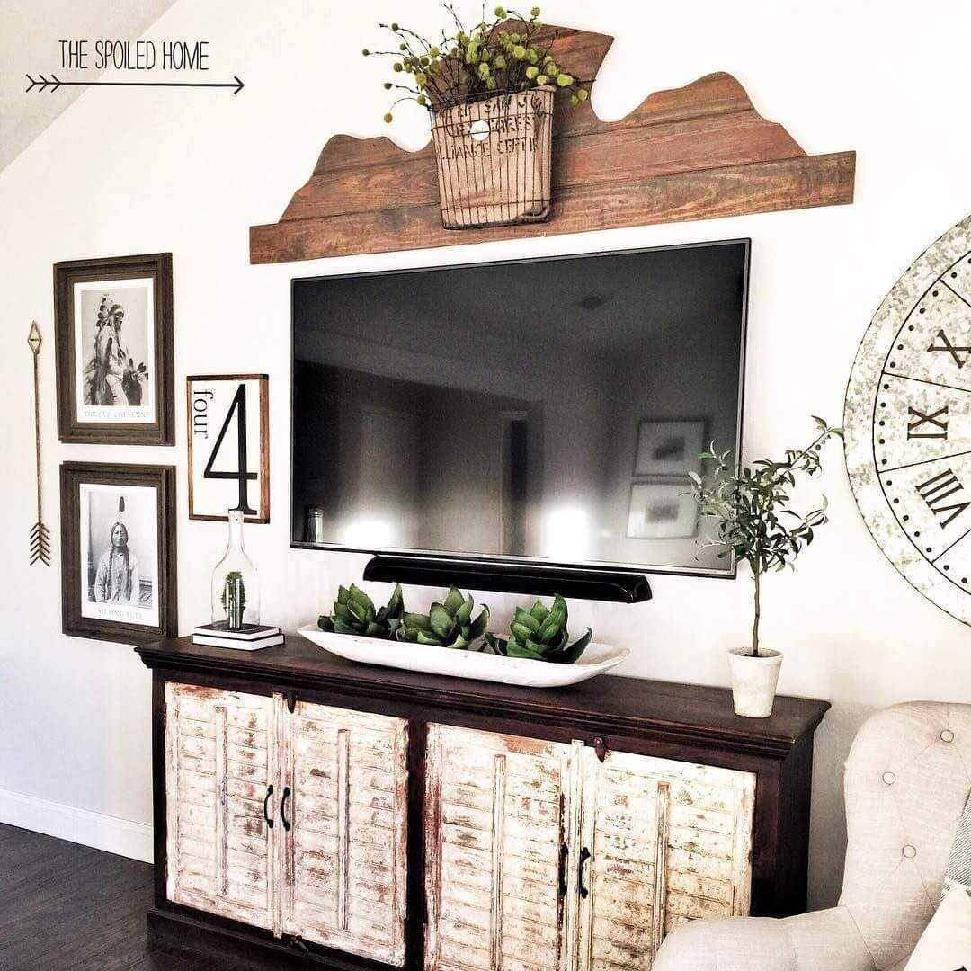 Here we have a great example of how you could turn an otherwise ordinary TV are into a rustic décor showpiece. Over the TV they created a wooden piece by cutting a pattern out of a series of rustic tongue and groove boards. Then they hung a burlap basket with dried greenery in the center. To create balance, they mounted an oversized clock with roman numerals on one side. The other side has Native American themed prints, a metal arrow, and a number 4 print.