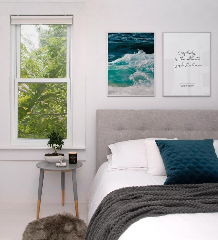 Minimalist bedroom with posters of ocean waves and da vinci's quote