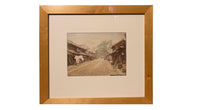 framed photograph of dirt road and village