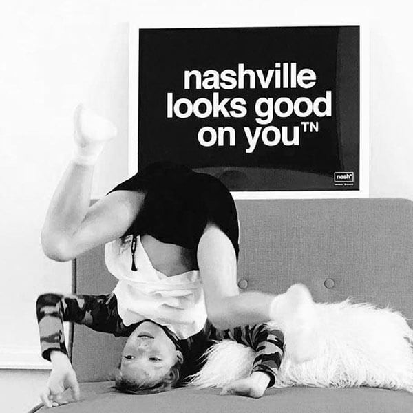 kid playing upside down on couch below a black nashville looks good on you poster