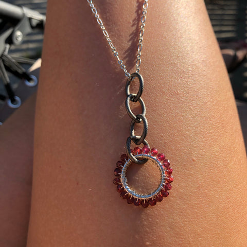 Garnet circle pendant. Sterling silver on long chain