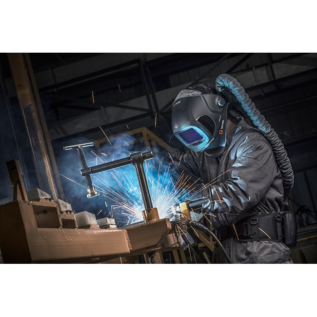 Welder using the Tecmen FreFlow V3 welding helmet with PAPR powered air purifying respiratory