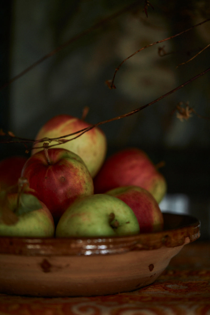 Red apples in a rustic pottery bowl in a vintage interior