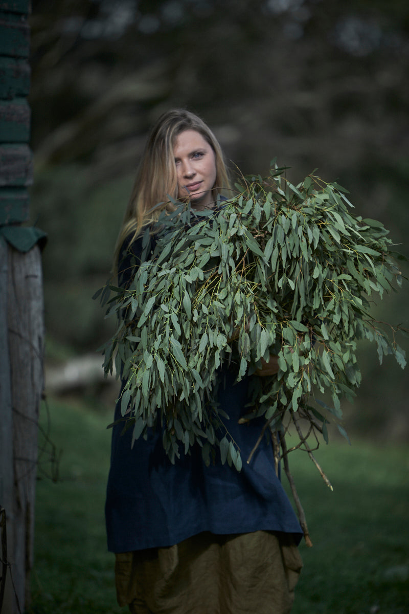 Pretty blonde woman holding a large bunch of eucalyptus