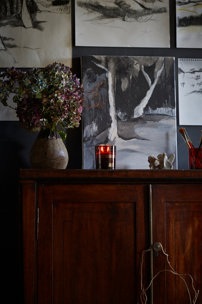 Interior detail of a vase of flowers, Southern Wild Co scented candle, art and paintbrushes on an antique sideboard