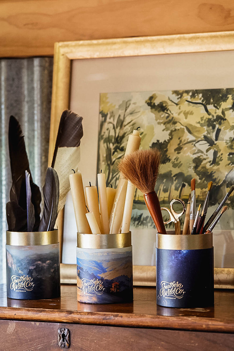 A collection of feathers, beeswax candles and artists paintbrushes