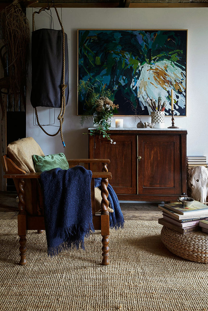 A vintage interior featuring a vibrant Skye Llewellyn painting, horse skull, books and Southern Wild Co scented candle