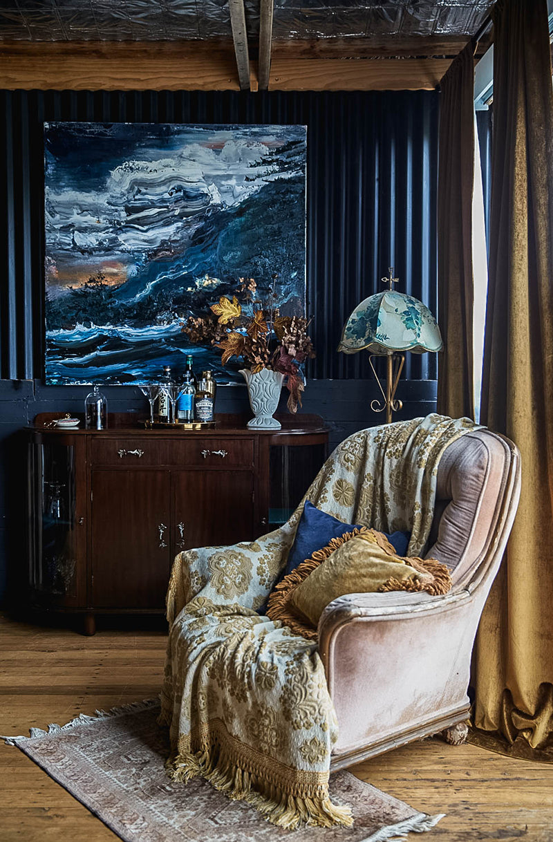 A home bar with Paul Ryan painting and vintage velvet chair at the Southern Wild Co shedquarters