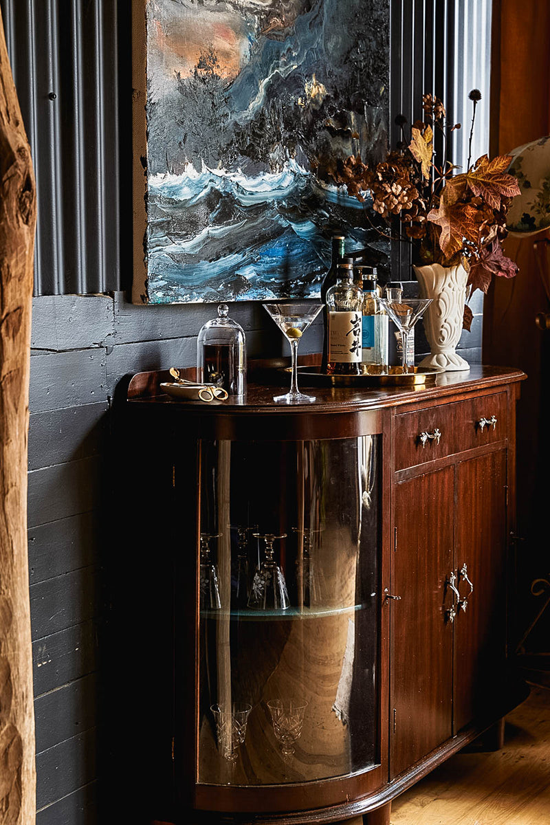 A home bar set up on a 1940's sideboard. There is a Paul Ryan painting on the wall and autumn dried flowers in a vintage vase.